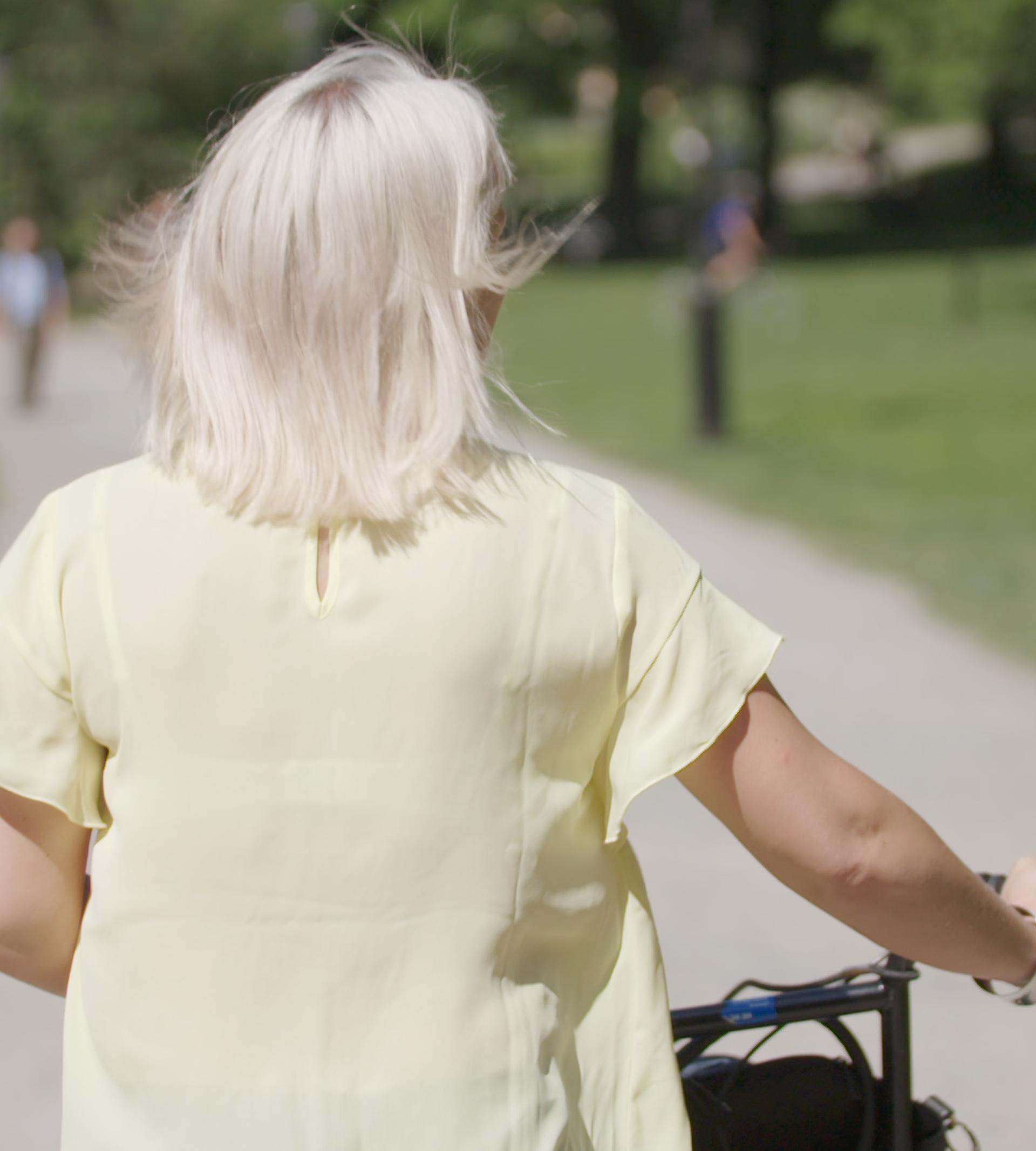Kvinna med cykel i park