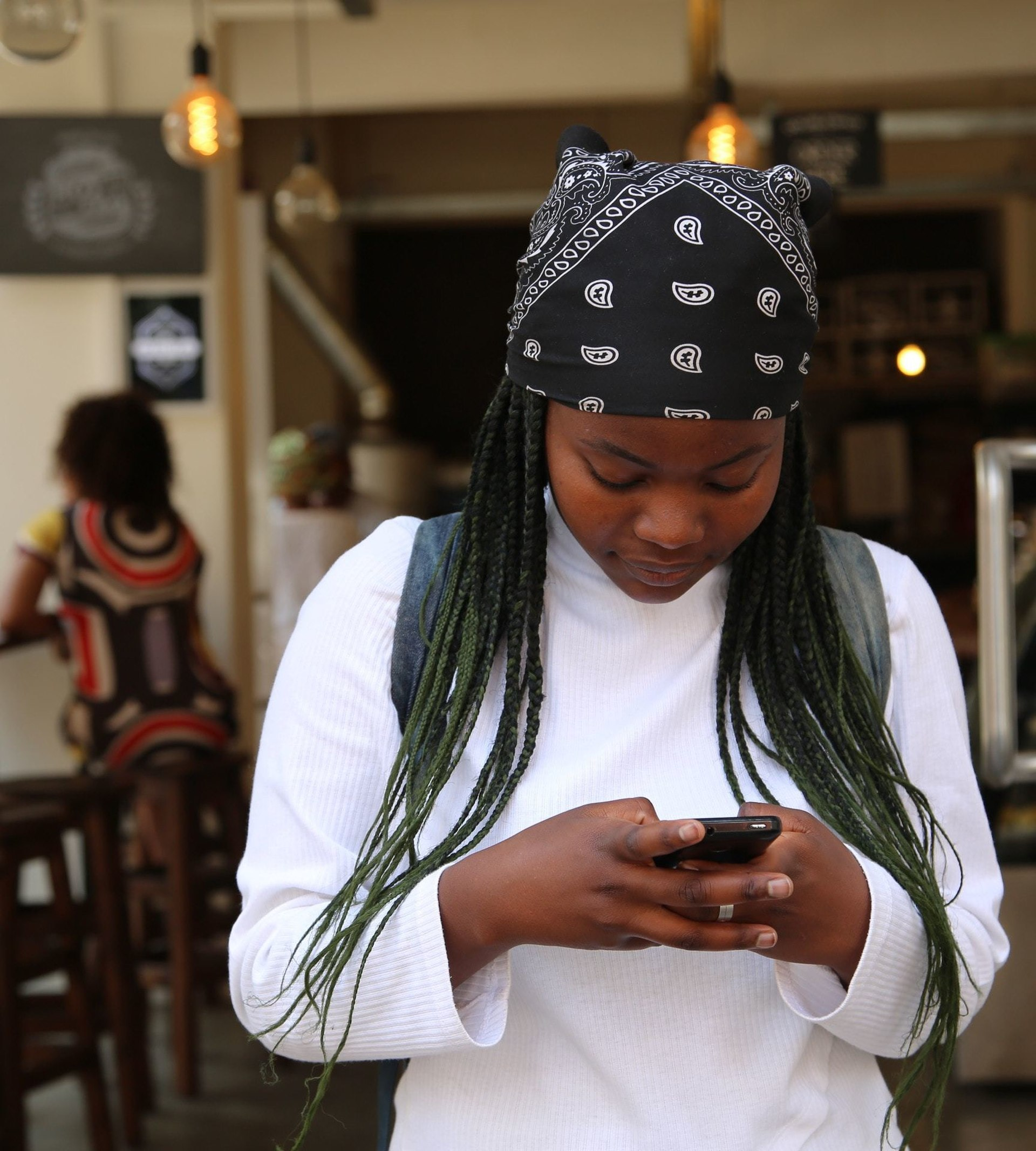 girl holding phone at cafe